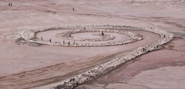 People walk along the spiral jetty on the Great Salt Lake Sept. 17, 2004. The black rocks of the jetty are covered in salt. Griffin/photo